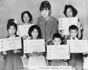 April Lou, teacher at Public School 1 in lower Manhattan, with six children who had recently arrived from Hong Kong and Taiwan in 1964, holding up placards giving his or her Chinese name (both in ideographs and in transliteration) and the name to be entered upon the official school records. Photo credit: Fred Palumbo.