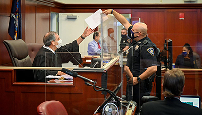 A court officer reaches around the plexiglass divider to pass documents to a judge. Plexiglass surrounds all public facing areas in the courtroom.